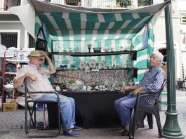 Stand de vajilla atendido por dos señores sentados en la feria de San Telmo